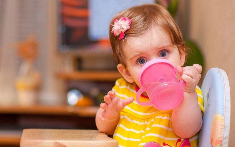 Ребенок в 8 месяцев держит кружку
